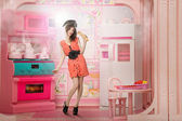 Young woman like a doll cokking in pink kitchen — Stock Photo