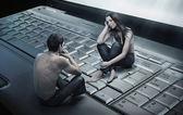 Fotografía conceptual de una pareja sentada en portátil — Foto de Stock
