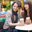Two beautiful women drinking coffee and chatting — Stok fotoğraf