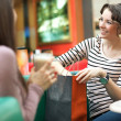 Stunning women after shopping talking with friend — Stock Photo