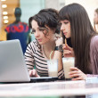 Two young girls watching something on notebook — Stock Photo #5087660