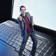 Conceptual photo of a happy man standing on the laptop's keyboar — Stok fotoğraf