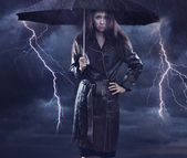 Single woman wearing coat holding umbrella. Creative szmbol of t — Stockfoto