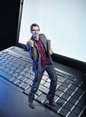 Conceptual photo of a happy man standing on the laptop's keyboar — Stock Photo