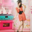 Doll like woman in doll house kitchen - Stock Photo