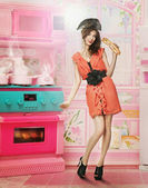 Doll like woman in doll house kitchen — Stock Photo