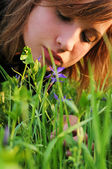Girl bent over to the flower — Stock Photo