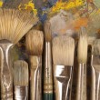 Artist's brushes on pallet — Stock Photo