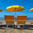 Lounge chairs under a yellow umbrella - Stock Photo