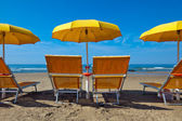 Lounge chairs under a yellow umbrella — Stock Photo