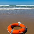 Red lifebuoy lying on the sand on the beach — Stock Photo #3420096
