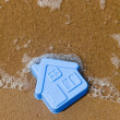 Plastic toy house lies on the sand - Stock Photo