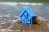 Toy plastic house on the sand washes wave — Stock Photo
