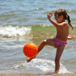 The little girl on the beach hit the ball — 图库照片