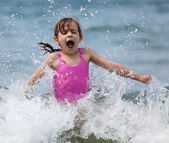 Little girl laughing and crying in the spray of waves — Stock Photo