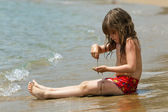 The little girl is sitting on a beach in the waves — Stock Photo