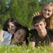 Four young men - two girls and two guys lying on the grass in th — Stok fotoğraf
