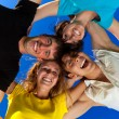 The four friends, embracing, has formed a circle and bent over a — Stock Photo