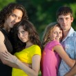 Four young embrace and stand in the park — Stock Photo