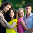 Four young embrace and stand in the park — Stock Photo #3497605
