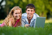 A couple relaxing in the park with a laptop — Stock fotografie
