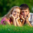 Couple resting on the grass in the park — Stock Photo #3773334