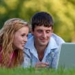 A couple relaxing in the park with a laptop — Stock Photo #3773352