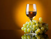 A glass of white wine and a bunch of green grapes — Stock Photo