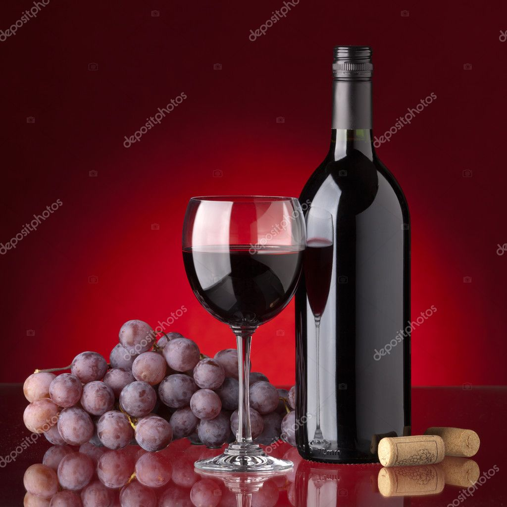 Bottle and glass of red wine, grape and cork on a red background — Stock Photo #3862131
