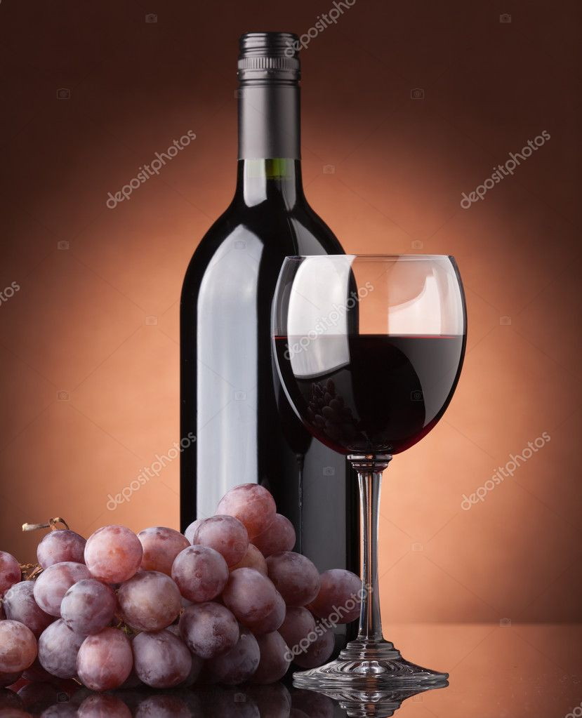 A bottle of red wine, glass and grapes on a brown background — Stock Photo #3864688