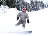Snowboarder guy sliding on the slope. — Stock Photo