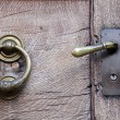 Doorknob and knocker on old wooden door — Stock Photo