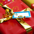 Red Christmas present with gold ribbon and tag — Stock Photo