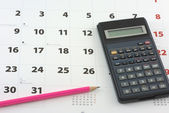 Calculator and pencil on the calendar — Stock Photo