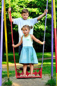 The boy and the girl on a swing — Stock Photo