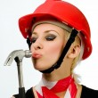 A girl with a hammer and a construction helmet — Stock Photo