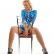 The beautiful blonde posing with a chair — Stock Photo