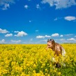 Girl in yellow flowers — Stock Photo