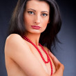 Beautiful dark haired girl with red beads — Stock Photo