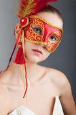 Beautiful young woman wearing red carnival mask — Stockfoto