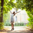 Young woman arms raised enjoying the fresh air in green forest. - Stock Photo