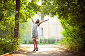 Young woman arms raised enjoying the fresh air in green forest. — Stock Photo