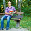 Handsome guy with bouquet waiting for his girlfriend outside — Stock Photo
