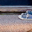 Blue Tennis Shoes on Door Mat - Stock Photo