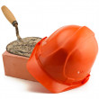 Orange helmet red brick and rusty bricklayer's trowel - Stock Photo