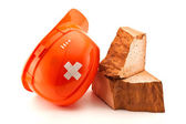 Orange helmet with cross shaped court plaster and broken brick — Stockfoto