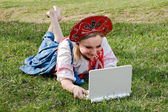 Girl in national clothes with a laptop on the grass — Stock Photo