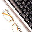 Fragment of keyboard with glasses — Stock Photo