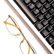 Stock Photo: Fragment of keyboard with glasses
