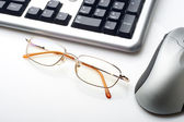 Keyboard mouse and glasses — Stockfoto